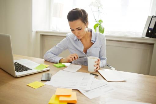 Fiatal, csinos nő ül az íróasztalánál, olvas és jegyzetel.
