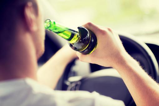 Egy férfi sört iszik vezetés közben.