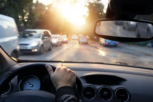 Egy sofőr autót vezet alkonyatkor.