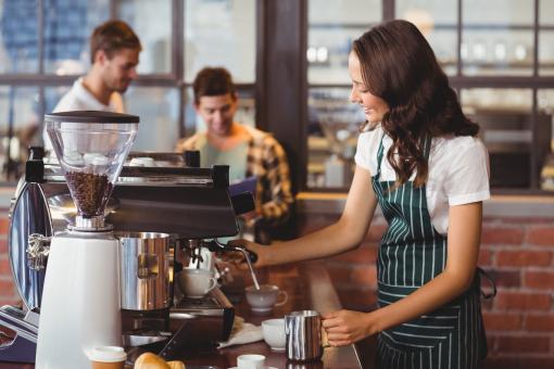 Egy fiatal pincérnő kávét készít a kávézóban.