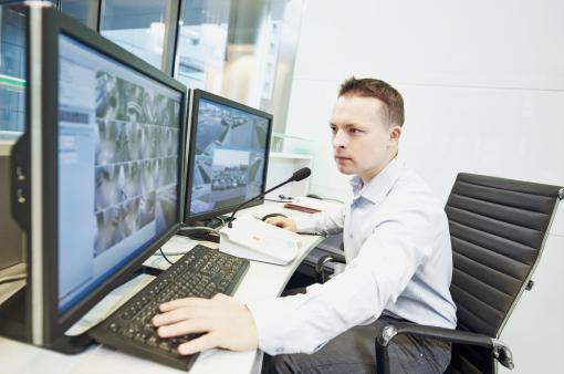 Egy biztonsági őr a képernyőkön a megfigyelőkamerák felvételeit nézi.