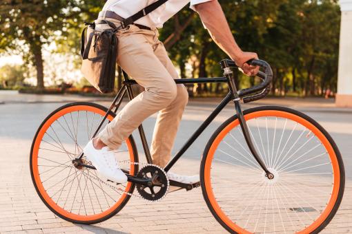 Fiatal férfi biciklivel közlekedik reggel. A kép vágva van, nem látszik a teljes teste.