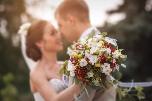 Ifjú férj és feleség ölelkezik az esküvőn. Előtérben egy esküvői csokor.