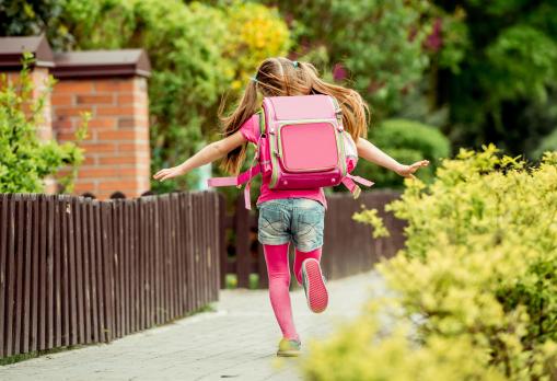 Egy kislány iskolás táskával a hátán iskolába siet.