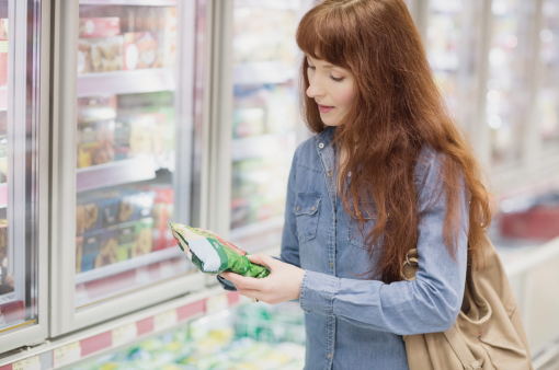 Egy vásárló fagyasztott zöldséget vásárol a boltban.