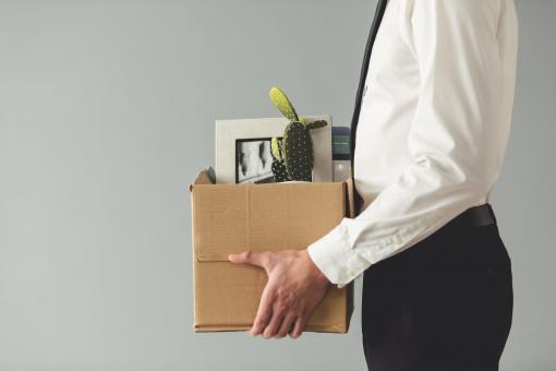 Egy férfit kirúgtak a munkahelyéről. Egy dobozt tart a kezében, amiben a személyes holmijai vannak.