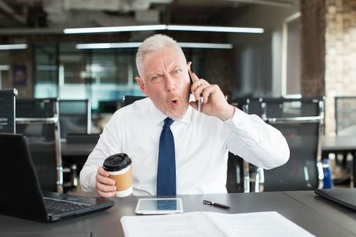 Ideges üzletember telefonon beszél az irodában.