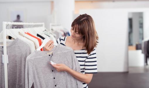 Egy fiatal nő a boltban egy szürke pulcsit és annak az árát nézegeti.