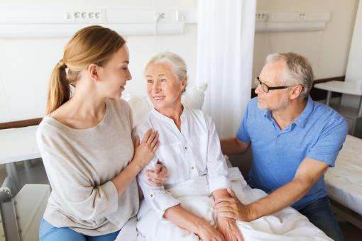 Egy idő nő fekszik a kórházi ágyon. Egy idős férfi és egy fiatal lány, valószínűleg a rokonai, mellette vannak és gondoskodnak róla.