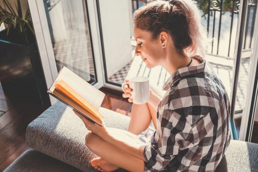 Egy fiatal csinos lány az ablakpárkányon ül, olvas és kávét iszik.