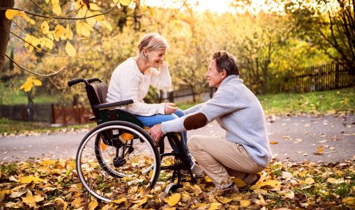 Idős házaspár a parkban, a feleség kerekesszékben van.