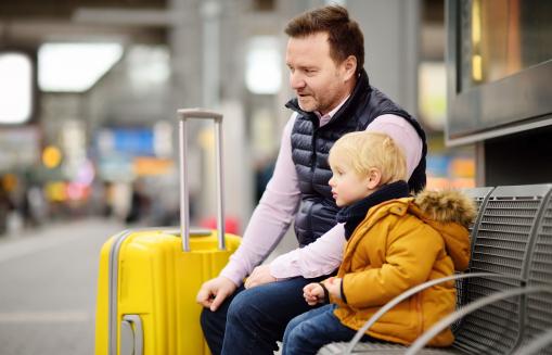 Egy apa és a szőke kisfia ülnek a vonatállomás várótermében és várják a vonatot. Mellettük egy nagy sárga gurulós bőrönd van.