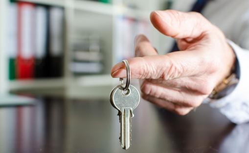 Egy öltönyös férfi kulcscsomót tart a kezében.