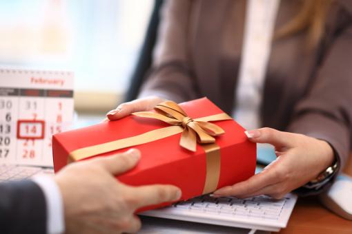 Egy üzletember ajándékot ad egy nőnek.