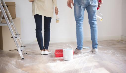 Egy férfi és egy nő festőhengerrel áll az új házban.