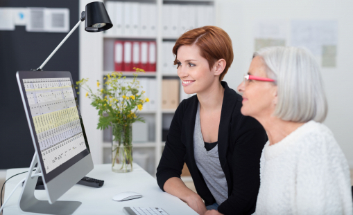 Egy fiatal és egy idős hölgy ül az irodában a számítógép előtt.