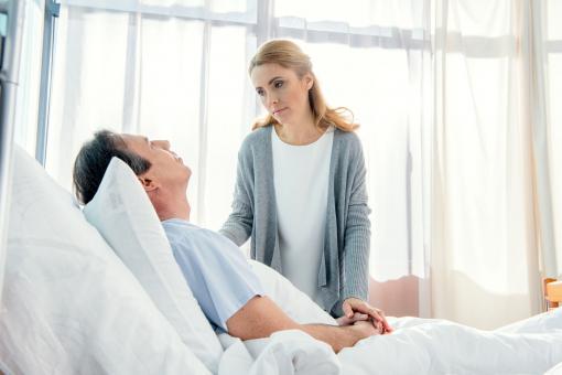 A feleség a beteg férje ágya mellett áll.