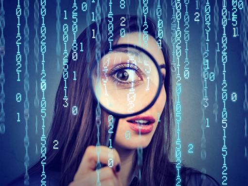 Egy nő nagyítóval néz vizsgálja a bináris kódrendszert.