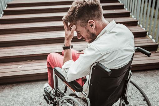 Egy kerekesszékben ülő férfi a lépcső előtt áll. Nem tud felmenni.