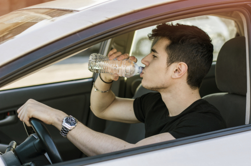 Egy fiatal férfi autót vezet és palackozott vizet iszik.