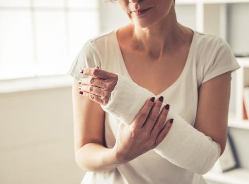 Egy nő begipszelt kézzel ül az orvosi rendelőben.
