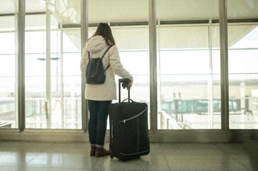 Egy nő áll a reptéren és néz ki az ablakon. Kezében egy gurulós bőrönd, hátán hátizsák.