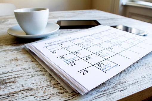 Az asztalon van egy naptár, egy csésze kávé és egy telefon.