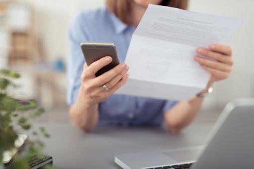 Egy nő egy levelet és egy telefont tart a kezében és tárcsáz.