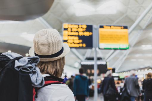 Egy nő a reptéren várakozva nézi a kijelzőt és az úti célokat.