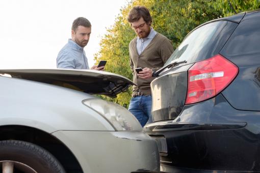 Két férfi összeütközött autóval. Autóik mellett állva telefonálnak.