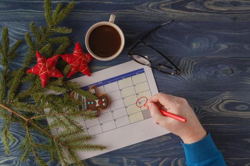 Az asztalon van egy naptár, fenyőágak, karácsonyfadíszek. A december 25. be van karikázva.