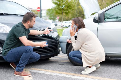 Két autó egymásnak ütközött. A két sofőr, egy férfi és egy nő veszekedik és segítséget hív telefonon.