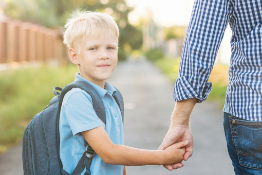 Az apa fogja a fia kezét, és iskolába kíséri.