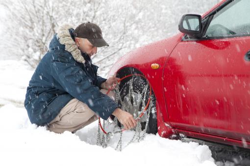 Egy férfi hóláncot szerel az autó kerekére.
