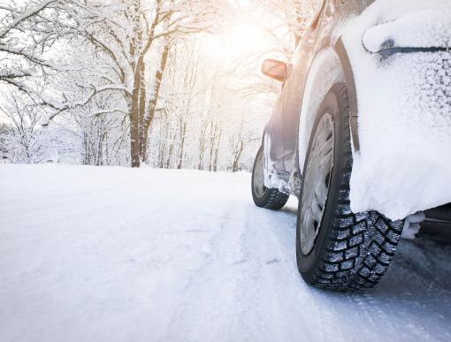 Egy autó a havas úton közlekedik.