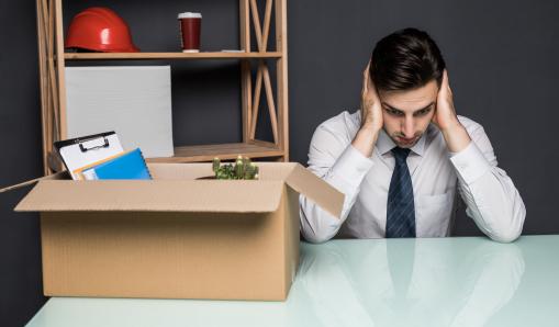 Egy fiatal üzletember ül az irodában az asztalánál, előtte egy személyes dolgokkal tele doboz van.