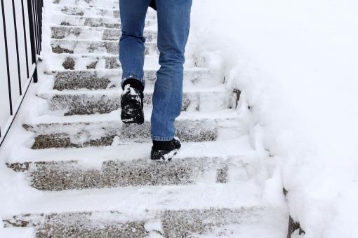 Egy ember lépcsőzik a jeges és havas lépcsőn.