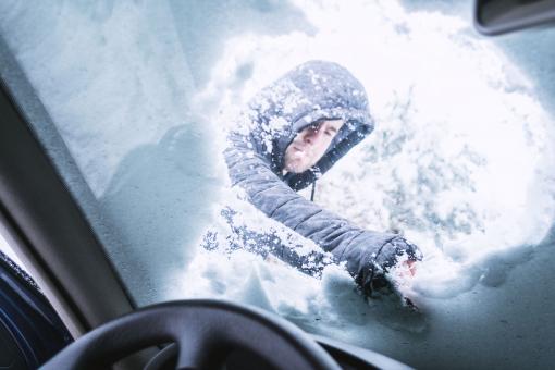 Egy férfi az autó szélvédőjéről takarítja le a havat. A kép az autó belsejéből készült.