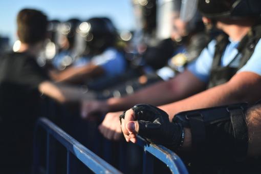 Tüntetés alatt a rendőrök a korlátnak támaszkodnak.