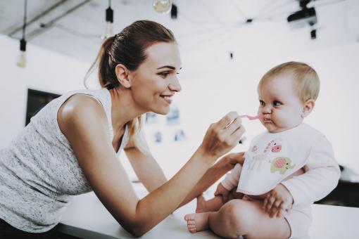 Egy világos hajú nő a gyerekét eteti a konyhában.
