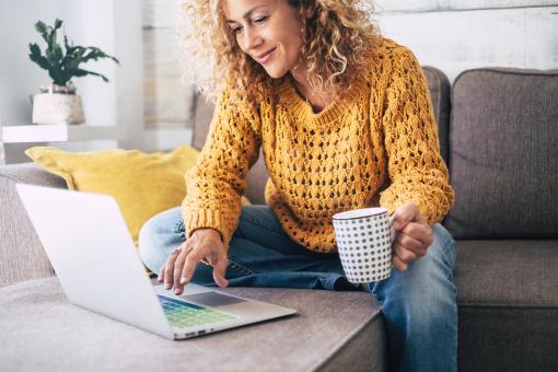 Egy szőke, göndör hajú nő a kanapén ül, kezében egy kávéval. A laptopján dolgozik.