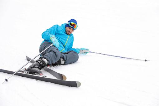 Egy síelő férfi elesett a hóban.