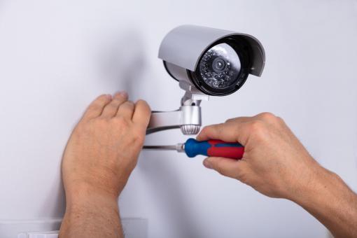 Egy szakember biztonsági kamerát szerel fel a falra.