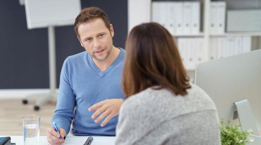 Az irodában egy férfi és egy női kolléga beszélgetnek az asztalnál.