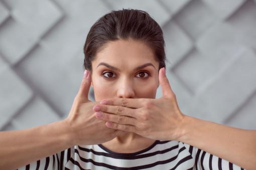 Egy nő eltakarja a száját a tenyerével. Társadalmi problémára, emberi jogokra utaló kép.