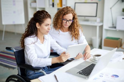 Két fiatal nő dolgozik az irodában. Az egyikük kerekesszékben ül.