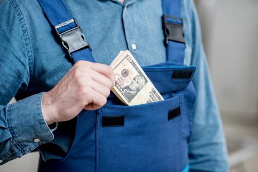 Egy munkásember a zsebébe csúsztat egy pénzköteget.