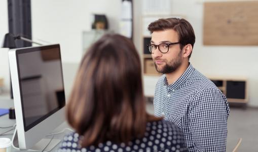Az irodában a beosztott a főnökével beszélget a számítógép előtt.