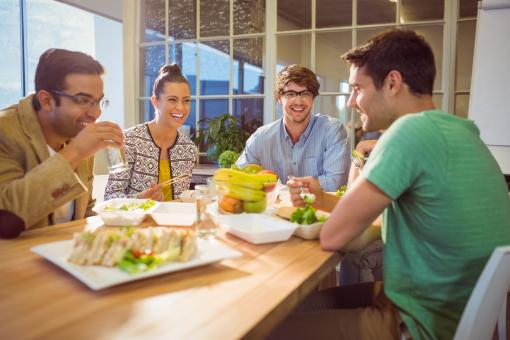Fiatal kollégák együtt ebédelnek az irodában.
