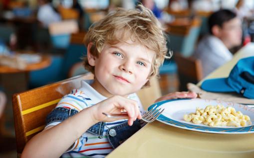 Egy szőke fiú kisgyerek tésztát eszik az óvodai étkezdében.